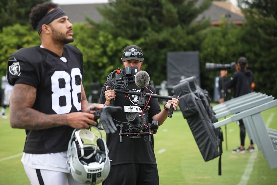 Film Connection grad Sam Freed in action, filming Raiders' WR Marcell Ateman in foreground.